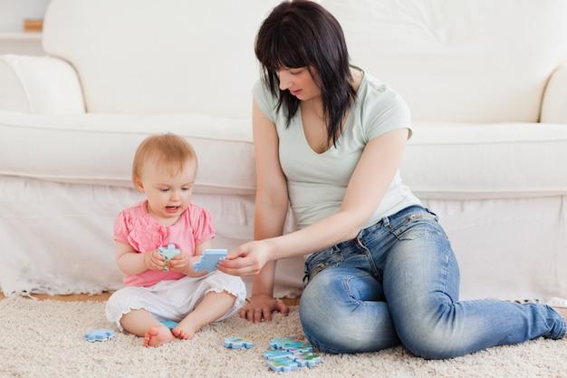 Mooie vrouw die haar baby in haar wapens houdt terwijl het zitten op een tapijt