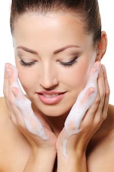 Mooie vrouw die haar gezicht met schuim op de heands wast