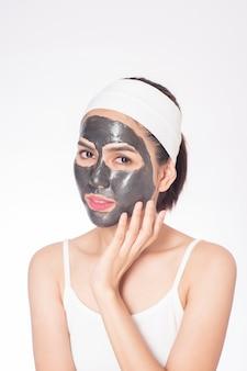 Mooie vrouw die haar gezicht op witte achtergrond maskeert