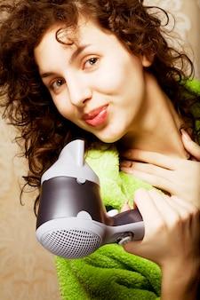 Mooie vrouw die haar haar met haardroger droogt