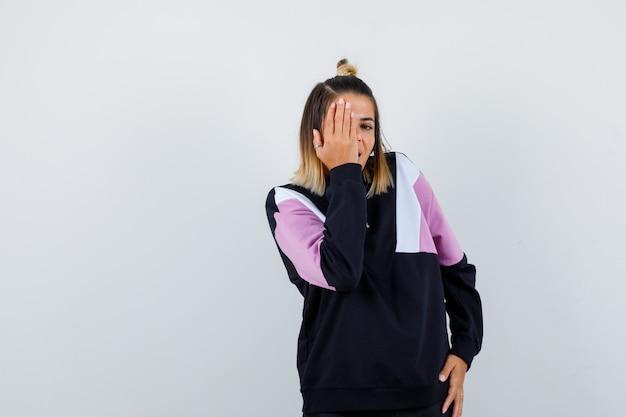 Mooie vrouw die haar hand in de gaten houdt in sweatshirt en er opgewonden uitziet