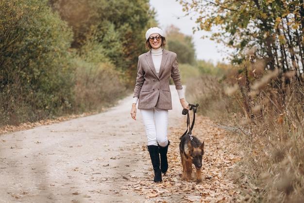 Mooie vrouw die haar hond in de herfstpark opstapt