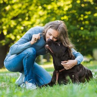 Mooie vrouw die haar hond in tuin kust