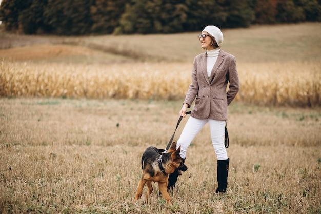 Mooie vrouw die haar hond op een gebied uitstapt