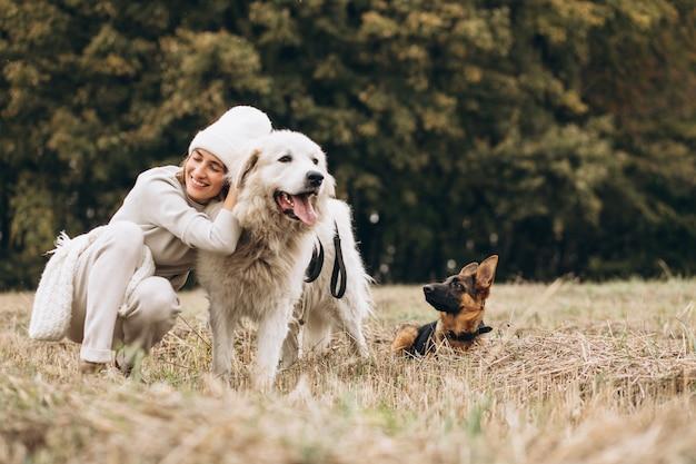 Mooie vrouw die haar honden op een gebied uitstapt