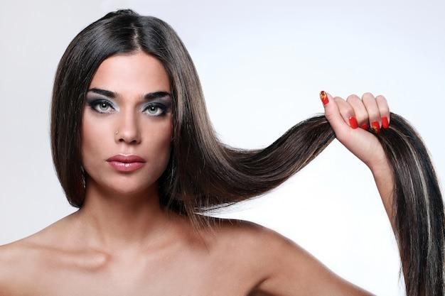 Mooie vrouw die haar lang haar toont