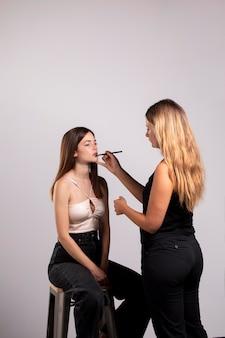 Mooie vrouw die haar make-up laat doen door een professional