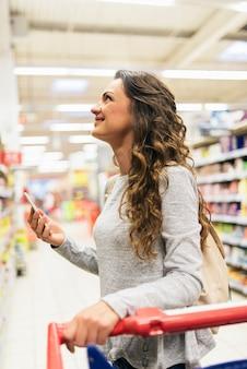 Mooie vrouw die haar mobiel in supermarkt gebruikt. marktvoedselconcept.