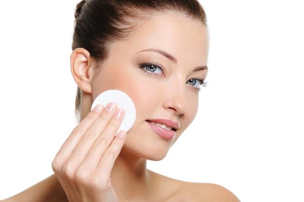 Mooie vrouw die haar mooi gezicht met wattenstaafje schoonmaakt - over witte achtergrond