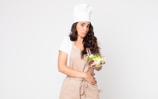 Mooie vrouw die haar schouders ophaalt, zich verward en onzeker voelt, een schort draagt en een salade vasthoudt