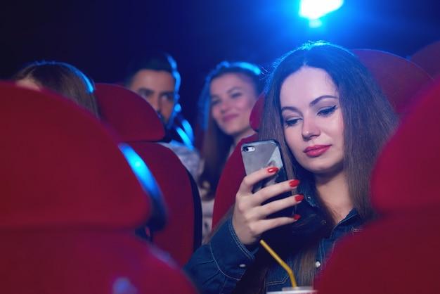 Mooie vrouw die haar telefoon met behulp van tijdens een saaie film bij de mededeling van de bioskoop copyspace technologie verveelde afleiding die online internet de verslaafde drager van de sociale gebruikersmobiliteit afleiden.