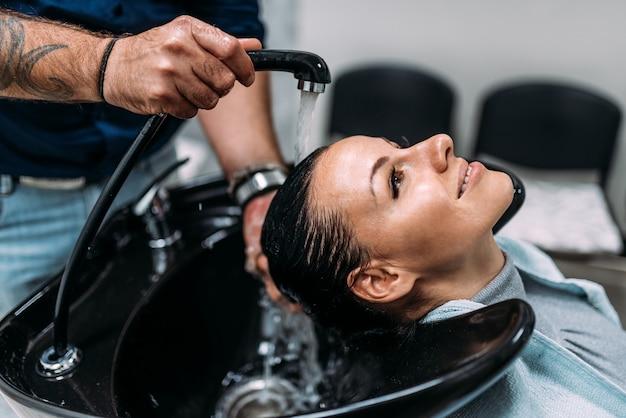 Mooie vrouw die haarbehandeling geniet.