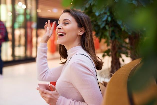 Mooie vrouw die hallo zegt en met haar hand zwaait
