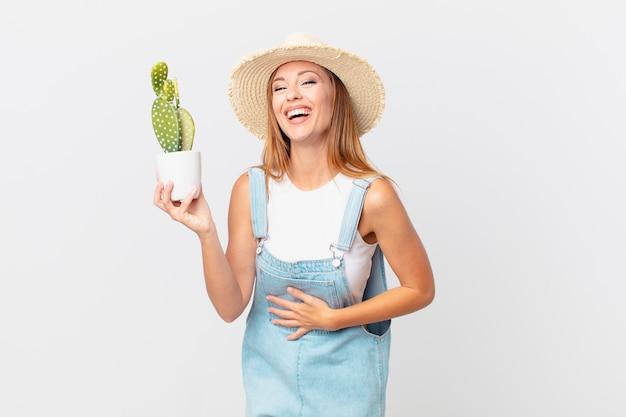 Mooie vrouw die hardop lacht om een hilarische grap en een decoratieve cactusplant vasthoudt