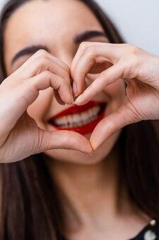 Mooie vrouw die hart met vingers maakt. mooie glimlach. rode lippen.