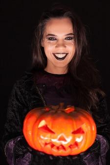 Mooie vrouw die heksenuitrusting voor halloween draagt die een griezelige pompoen over zwarte achtergrond houdt.