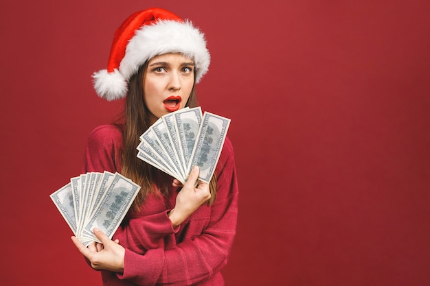 Mooie vrouw die het rode kostuum van de kerstman draagt dat en ventilator van geld in dollarbankbiljetten glimlacht houdt