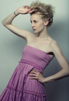 Mooie vrouw die het roze kledingsmodel stellen draagt