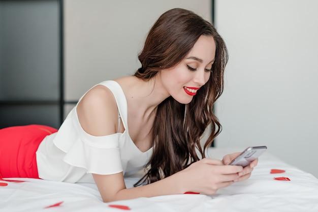 Mooie vrouw die het telefoonscherm in bed met hart gevormde confettien thuis bekijkt