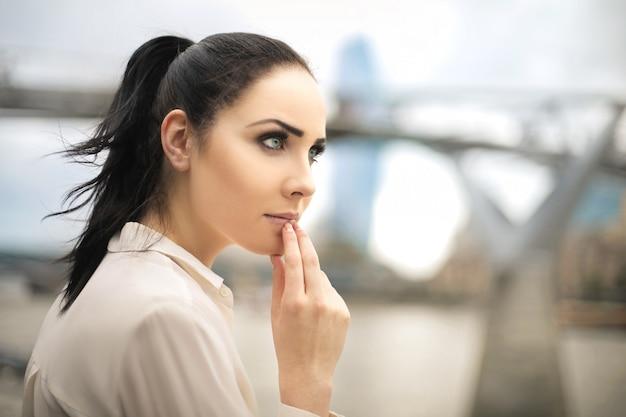 Mooie vrouw die het uitzicht bekijkt, dat over iets denkt
