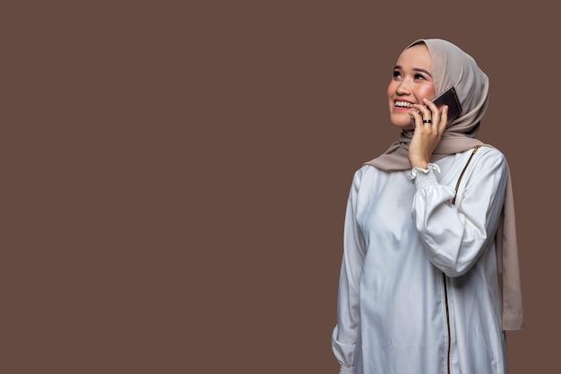 Mooie vrouw die hijab draagt, telefoneert met een lachende uitdrukking terwijl ze omhoog kijkt