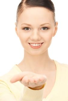 Mooie vrouw die iets op de palm van haar hand laat zien