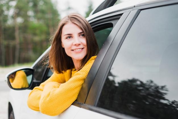 Mooie vrouw die in auto weg kijkt