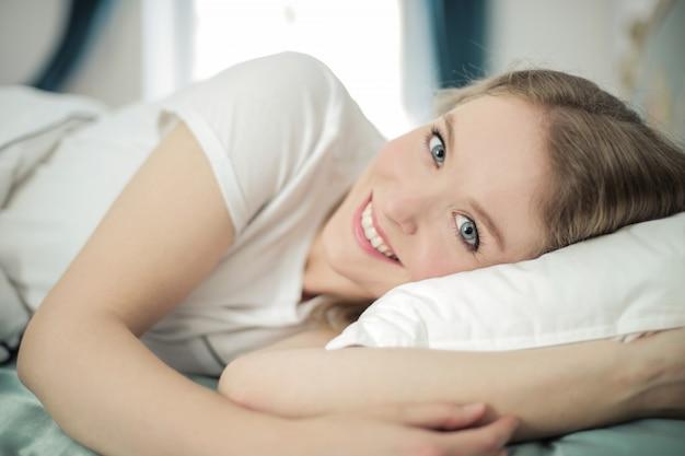Mooie vrouw die in bed glimlacht