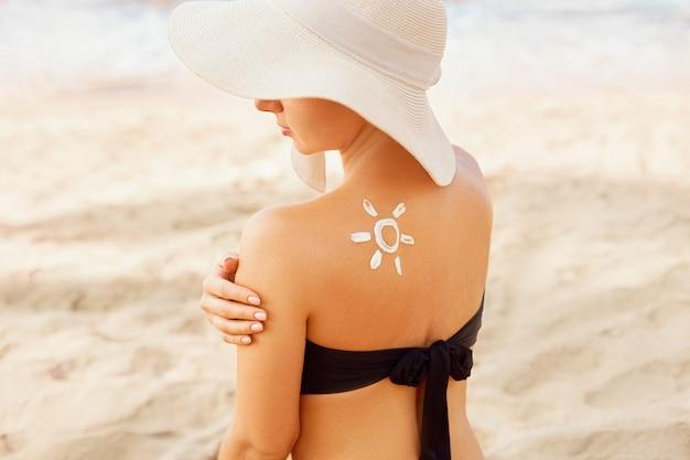 Mooie vrouw die in bikini zonnebrandcrème op gebruinde schouder toepast. zon bescherming. huid- en lichaamsverzorging