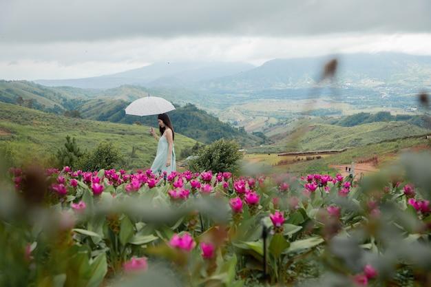 Mooie vrouw die in bloementuin loopt. natuurlijk landschap.