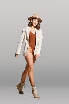 Mooie vrouw die in bruin romper, witte blazer, hoed en visnetlegging loopt