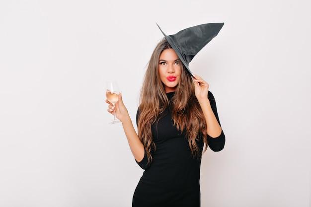 Mooie vrouw die in carnaval-hoed champagne drinkt