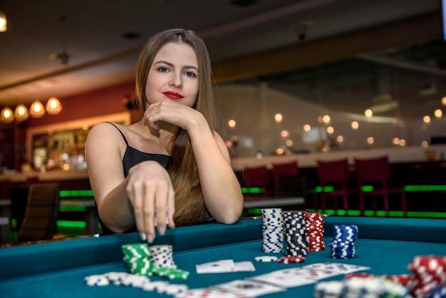 Mooie vrouw die in casino fiches van stapel neemt