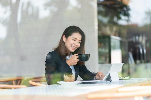 Mooie vrouw die in de koffie werkt