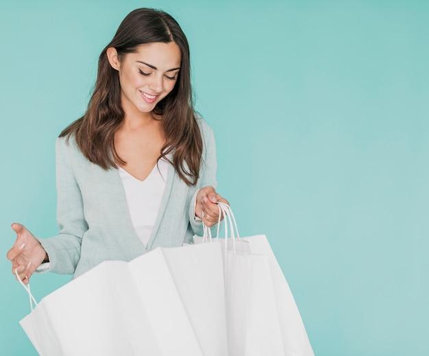 Mooie vrouw die in de winkelnetten kijkt