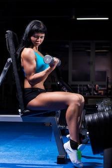 Mooie vrouw die in een gymnastiek uitwerkt