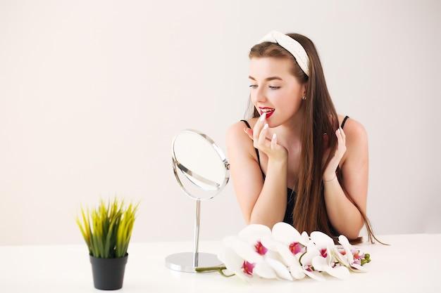 Mooie vrouw die in een spiegel dichtbij planten en bloemen kijkt