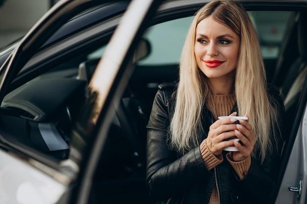Mooie vrouw die in haar auto zit en koffie drinkt