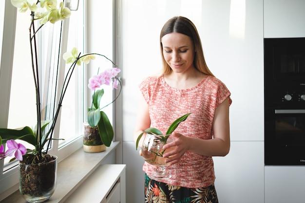 Mooie vrouw die in handen een blikje water met een orchidee plant