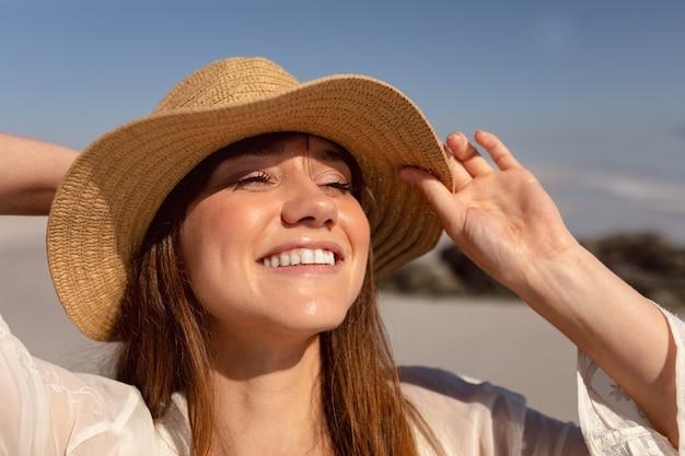 Mooie vrouw die in hoed weg op strand in de zonneschijn kijkt