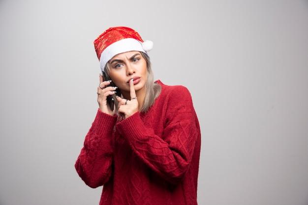 Mooie vrouw die in kerstmanhoed iemand op telefoon roept.
