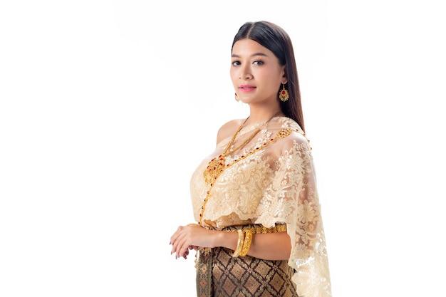 Mooie vrouw die in nationaal traditioneel kostuum van thailand glimlacht. isoleren