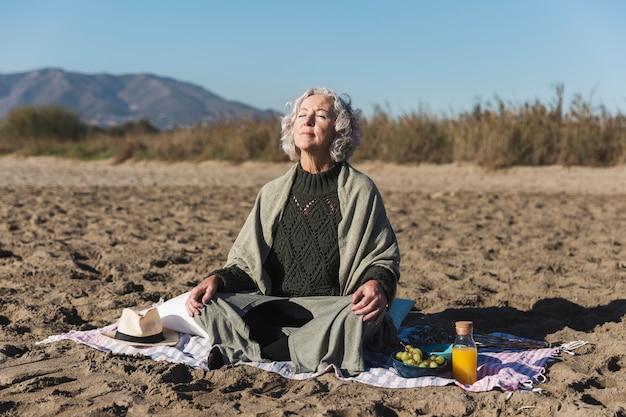 Mooie vrouw die in openlucht mediteert