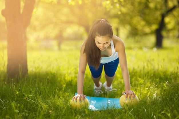 Mooie vrouw die in openlucht uitoefent. vrolijk slank meisje die training doen bij het park in de zomertijd. vrouw doet afslanken riem