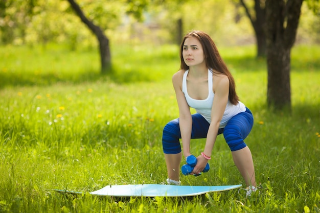 Mooie vrouw die in openlucht uitoefent. vrolijk slank meisje die training doen bij het park in de zomertijd