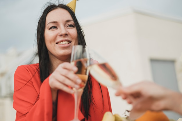 Mooie vrouw die in rode kleding omhoog een glas champagne toejuicht