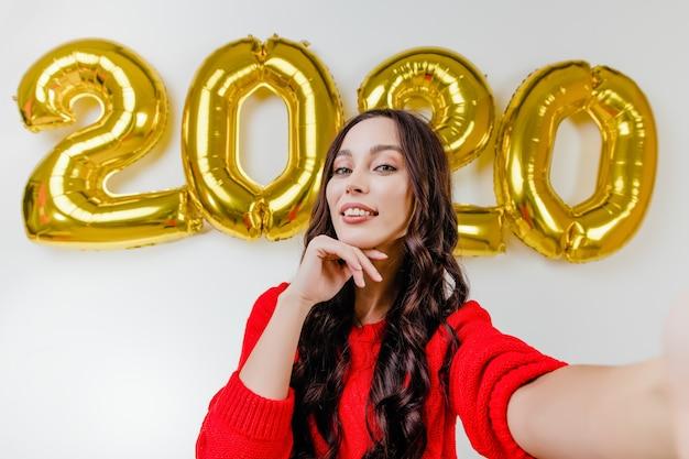 Mooie vrouw die in rode sweater grappige selfie voor 2020 nieuwe jaarballons maakt