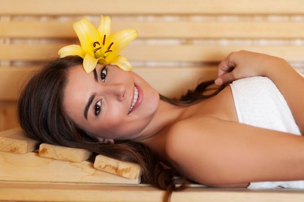 Mooie vrouw die in sauna ligt