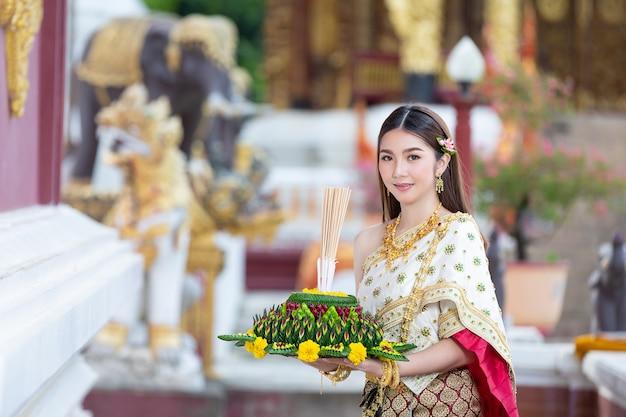 Mooie vrouw die in thaise traditionele uitrusting en zich bij tempel glimlacht bevindt