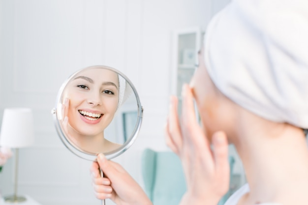 Mooie vrouw die in witte badjas en handdoek haar perfecte huid in spiegel bekijkt en tonale roombasis op gezicht toepast